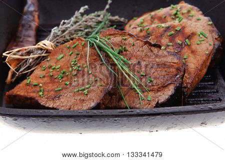 fresh ripe roasted beef meat on barbecue pan with thyme and pepper isolated on white background