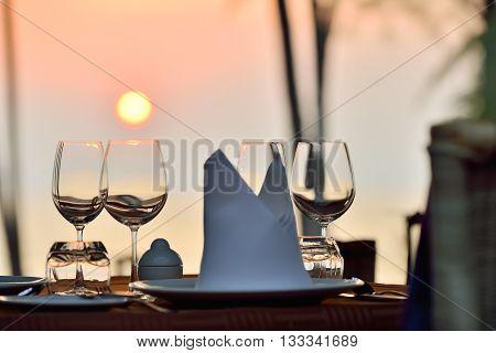 Romantic dinner table setup at a beach side restaurant on sunset.