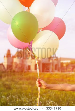 Young couple in love holding baloons on the sunset during summer evening.