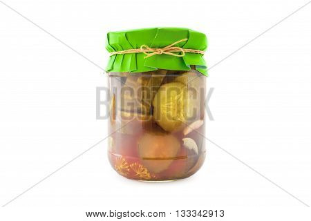 Homemade pickled sliced cucumbers in glass jar with green paper wrapper. Homemade preserves, pickles. Jar of canned sliced cucumbers isolated on white