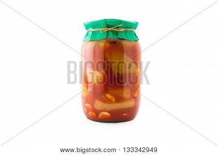 Homemade pickled peppers in tomato sauce in glass jar with paper wrapper. Homemade preserves, pickles. Jar of canned peppers in tomato sauce isolated on white