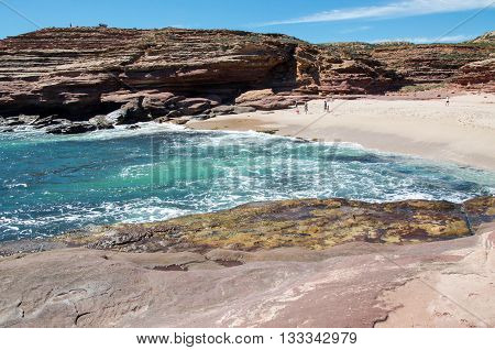 Pot Alley gorge with natural sandstone formations and turquoise-green Indian Ocean waters in a secluded beach under blue skies in Kalbarri, Western Australia.