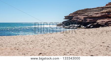 Glistening Indian Ocean waters in the bay at Pot Alley gorge with red sandstone under a clear blue sky in Kalbarri, Western Australia.