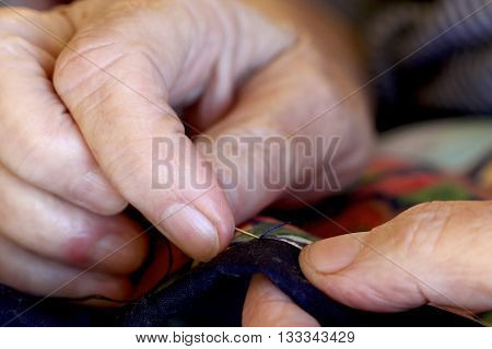 Hands and fingers stitching fabric with a needle and thread.
