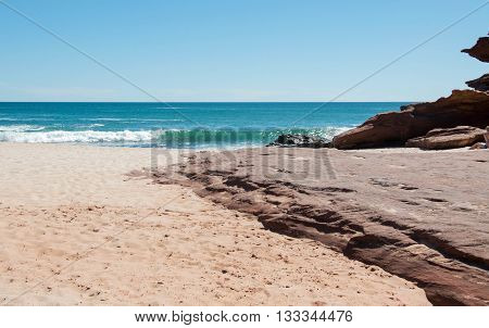 Secluded beach at Pot Alley with red sandstone formations and turquoise Indian Ocean waters under a clear blue sky in Kalbarri, Western Australia.