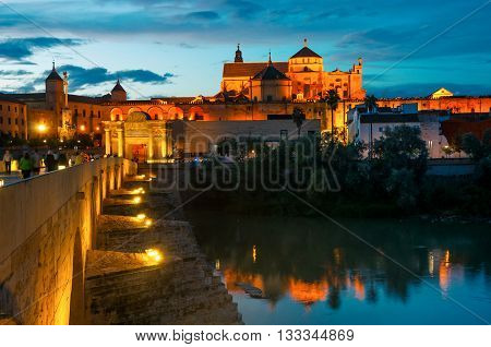 illuminated Roman bridge and La Mezquita at sunset in Cordoba, Andalusia, Spain. Guadalquivir river