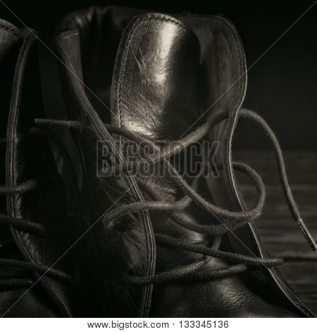 Black leather boots closeup on a black background closeup with copy space. Black and white toning