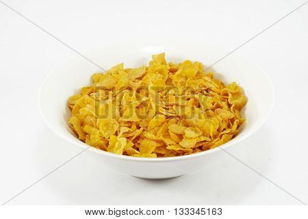 Bowl of cornflakes with a cup of milk; white background