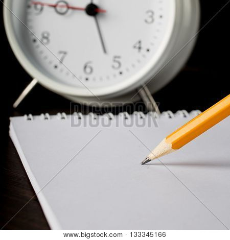 pencil writing on white paper closeup on black background. In the background is alarm clock. Time to work