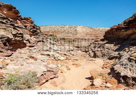 Sandy hiking path through the rugged red sandstone landscape in the gorge at Pot Alley under clear blue skies in Kalbarri, Western Australia.