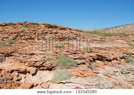 Red sandstone dotted with plants in the rugged terrain at the gorge at Pot Alley in Kalbarri, Western Australia on a clear day.