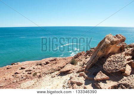 Overhead view from natural sandstone rock formations of the turquoise Indian Ocean waters at Pot Alley in Kalbarri, Western Australia on a clear sunny day.