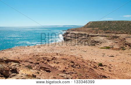 Overlooking the glistening turquoise Indian Ocean coast with red sandstone cliffs at Pot Alley in Kalbarri, Western Australia under clear blue skies.