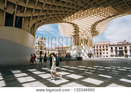 Seville, Spain - June 24, 2015: People walking near Metropol Parasol is a wooden structure located Plaza de la Encarnacion square, in old quarter of Seville, Spain