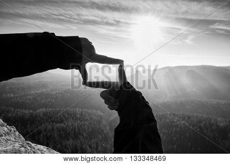 Female Hands Do Frame Gesture. Deep Misty Valley Bellow Sandsotne Cliff.  Sunny Spring Daybreak