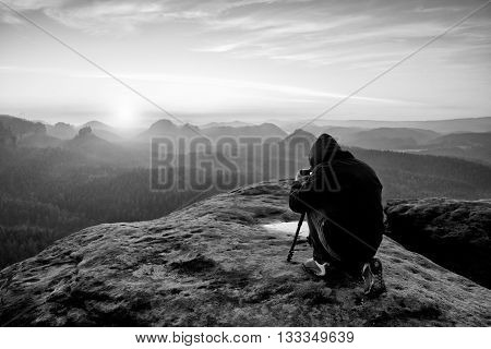 Professional On Cliff. Nature Photographer Takes Photos With Mirror Camera On Peak Of Rock.