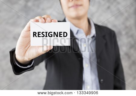Businessman Presenting Business Card With Word Resigned