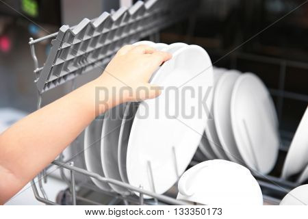 Little girl taking plates from the dishwasher, closeup