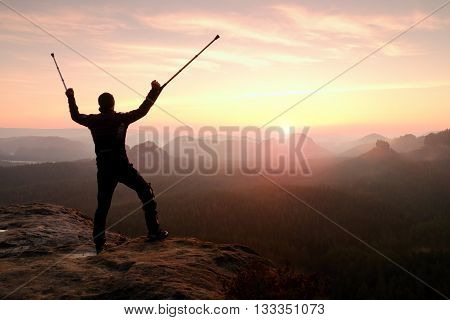 Man With Broken Leg And Medicine Pole Above Head Stay On Peak.