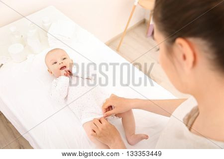 Mother and her little baby after bath in room