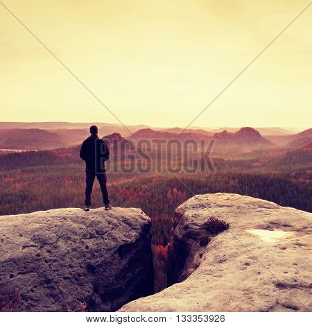 Silhouette Of Man On Sharp Cliff In  Mountains. Conceptual Scene.