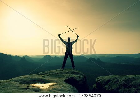 Happy Hiker With X Crossed Poles Above Head.  Foggy  Mountain Valley Bellow. Tall Tourist Enthusiast