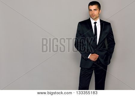 businessman in a suit on a gray background young male model in a black suit and tie