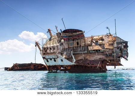 A photo with the broken rusty ship at red sea
