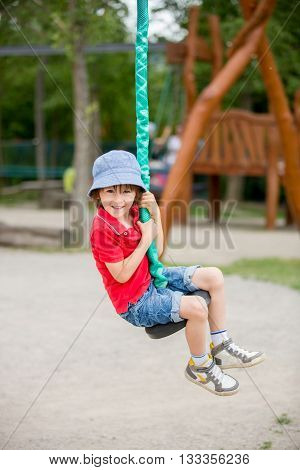 Cute Child, Boy, Rides On Flying Fox Play Equipment In A Children's Playground