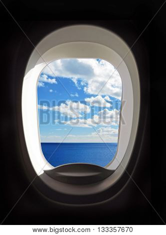 View outside of the airplane porthole to sea and clouds