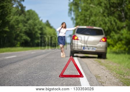 Woman calling for assistance after breakdown of her car on the road. Closeup on triangle warning sign.