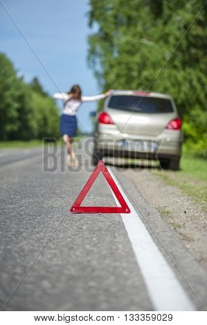 Red triangle warning sign and woman calling for assistance after breakdown of her car. Focus on triangle.