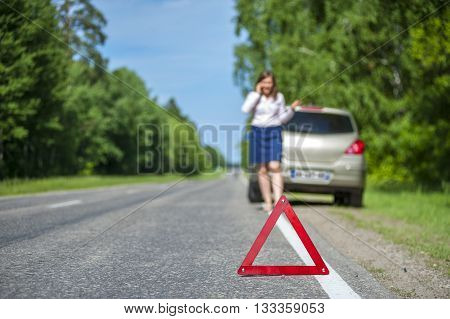 Young woman after breakdown calling to a car assistance. Focus on red triangle warning sign
