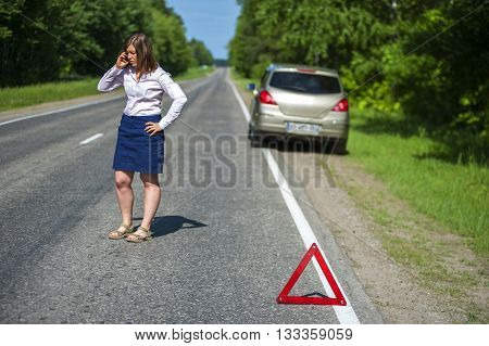 Female driver calling to a car assistance after breakdown. Broken car and red triangle warning sign