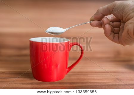 Hand Holds Teaspoon With Sugar Above Red Cup Of Tea. Unhealthy E