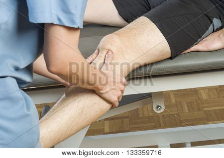 Chiropractor / physiotherapist is doing a knee massage.