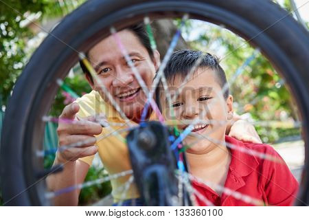 Cheerful Asian father looking at spinning wheel of bicycle