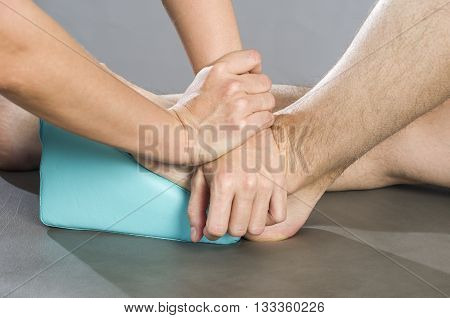Chiropractor /physiotherapist is doing a feet massage