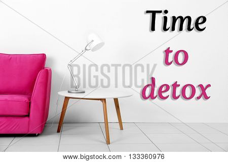 Living room interior with pink armchair, white table and lamp on white wall background