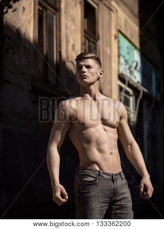 Man bare-chested young pose sexy model in jeans outdoor near building sunny day outdoor