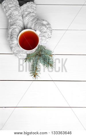 Female hands holding cup of hot drink, on wooden table background