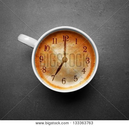 Cup of coffee on grey background, top view. Time concept