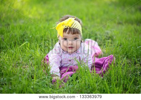Small cute baby girl with pretty face and funny eyes with yellow bow on head sitting on green grass outdoor on natural background