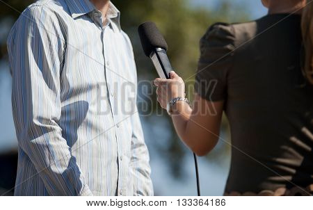 Press interview. Reporter making media interview using microphone.