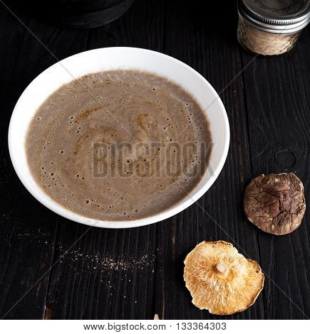 Close up of creamy vegan mushroom soup with champignon and shiitake in white bowl. Dark photo with black wood background. Dry shiitake mushroom on front.