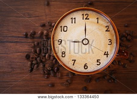 Brown ceramic cup of coffee decorated with roasted beans around on wooden background. Time concept