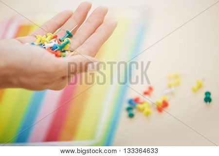 Close-up view on woman hand with colorful pushpins