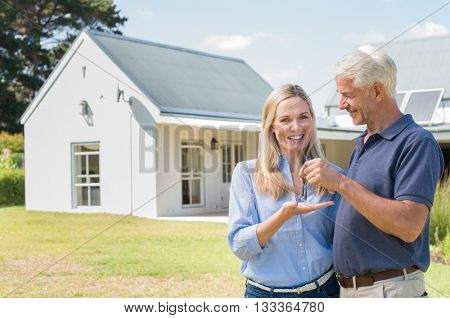 Cheerful senior couple standing outside their new house with keys. Retired man giving new house keys to his wife. Senior man and mature woman in the garden of their new house.
