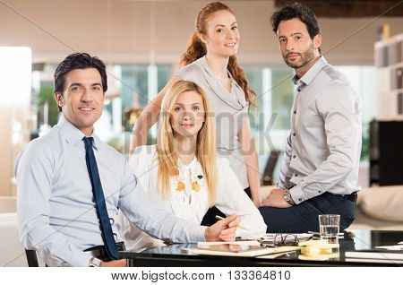 Successful business team looking at camera. Portrait of happy smiling businessmen and businesswomen posing for a annual report of company. Satisfied four colleagues around a business desk.