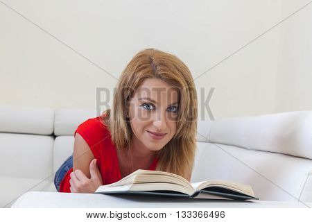 Woman reading a book laying on the couch and looking to the camera.